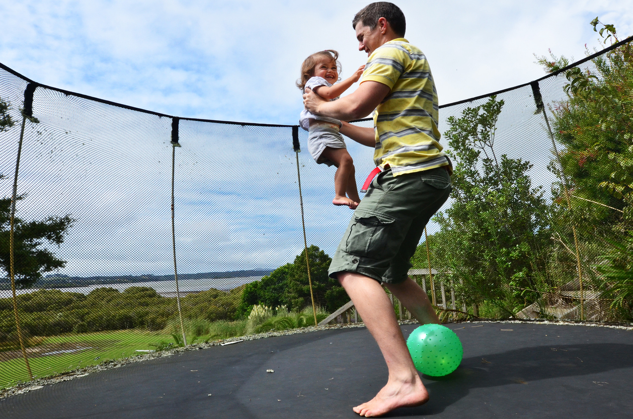 Father and his baby jumping together on a trampoline in Long Island, NY.